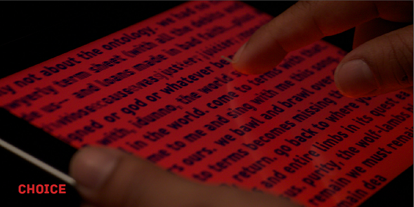 "Screen capture of ""No Choice About the Terminology"" by Jason Edward Lewis, Christian Gratton, Elie Zananiri and Bruno Nadeau. Photograph of a tablet displaying  a text in black font on a red background. It also shows someone's fingers touching the screen."