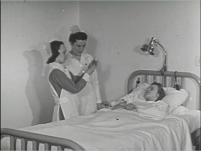 "Screen capture of ""Injections"" by Paul Bogaert. Two nurses tend to a bed-ridden patient. No text."